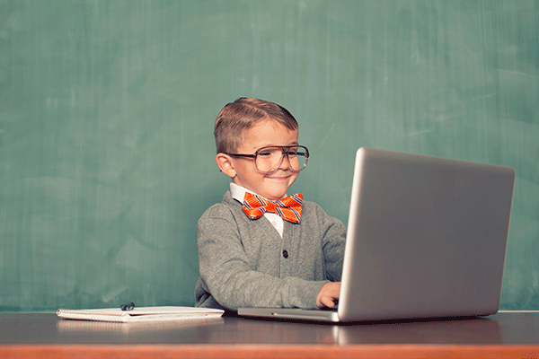 young boy with glasses and bow tie writing electronics blog on computer